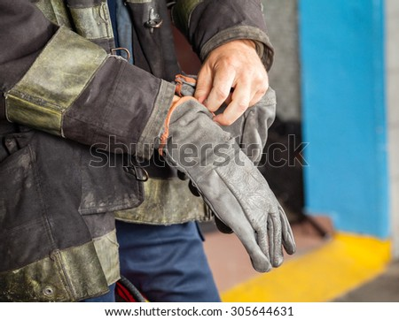 Midsection of male firefighter wearing glove at fire station - stock photo