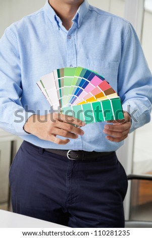 Midsection of male interior designer holding fanned out color swatches