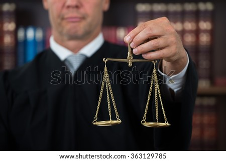 Midsection of male judge holding law scales in courtroom - stock photo