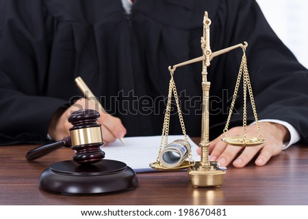 Midsection of male judge signing document with mallet and scale on desk - stock photo