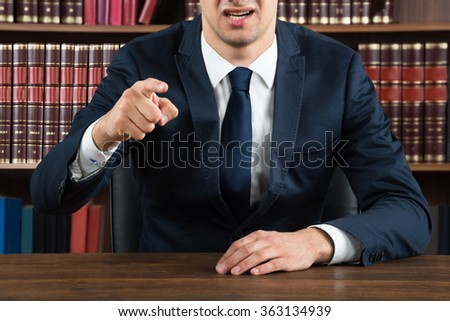 Midsection of male lawyer arguing while sitting at desk in courtroom - stock photo