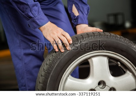 Midsection of male mechanic holding car tire at garage - stock photo