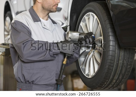 Midsection of male mechanic repairing car's wheel in workshop - stock photo