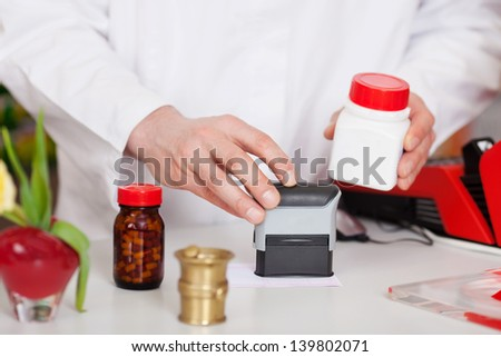 Midsection of male pharmacist stamping bill at pharmacy desk - stock photo