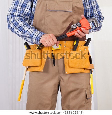Midsection of male repairman with tool belt holding adjustable wrench - stock photo