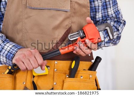 Midsection of male repairman with tool belt holding pipe wrench - stock photo