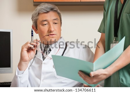 Midsection of male technician showing patient's file to mature doctor - stock photo