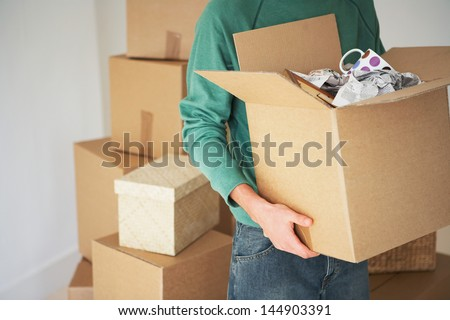 Midsection of man carrying open cardboard box in new home - stock photo