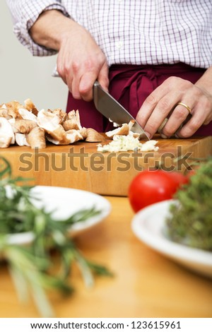 Midsection of man cutting mushrooms on wooden chopping board