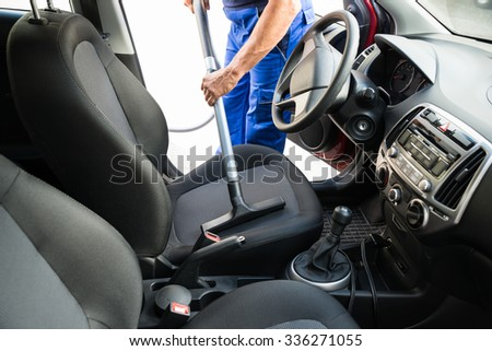 Midsection of man vacuuming car seat with vacuum cleaner