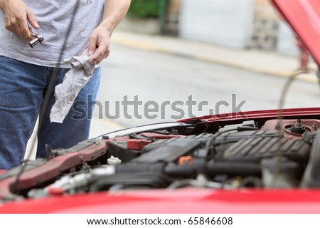 Midsection of man working under hood of car