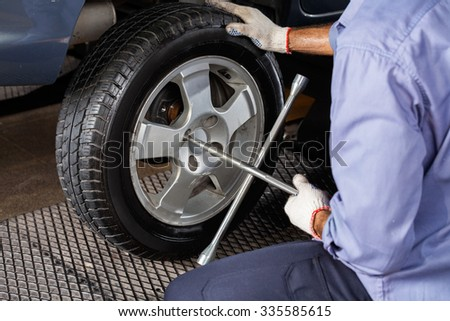 Midsection of mechanic fixing car tire with rim wrench at repair shop