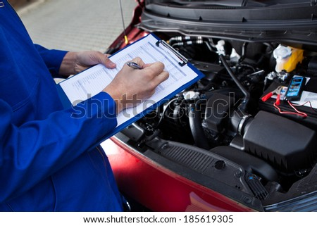 Midsection of mechanic holding clipboard in front of open car engine at street - stock photo