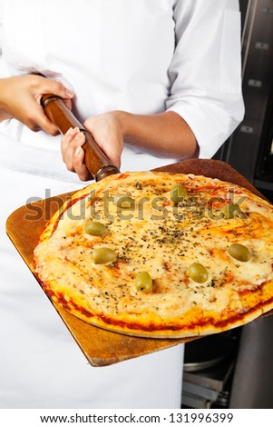 Midsection of mid adult female chef holding pizza on shovel - stock photo