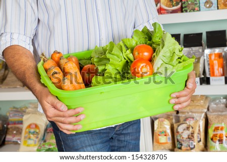 Midsection of mid adult man holding basket of fresh vegetables in supermarket - stock photo
