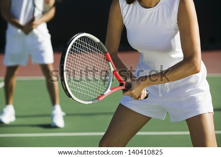 Midsection of mixed doubles tennis players on court with focus on woman - stock photo