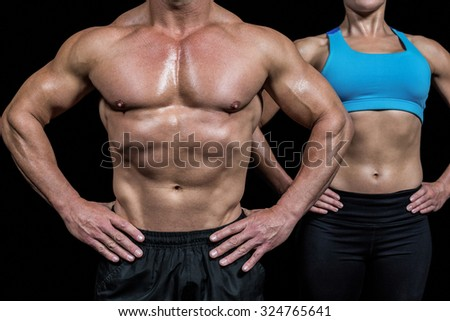 Midsection of muscular man and woman standing with hands on hip against black background - stock photo