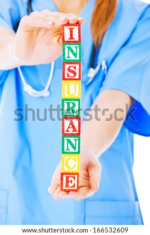 Midsection of nurse holding blocks spelling out insurance isolated over white background - stock photo