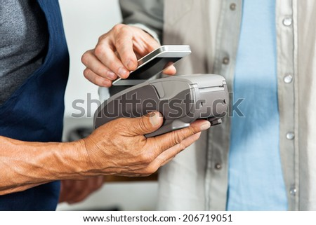Midsection of salesman accepting payment through NFC technology from customer in hardware store - stock photo