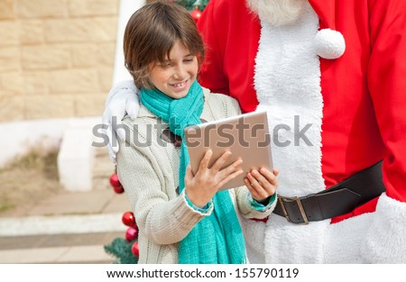 Midsection of Santa Claus and boy using digital tablet outdoors - stock photo