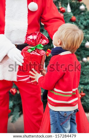 Midsection of Santa Claus giving present to boy outdoors - stock photo