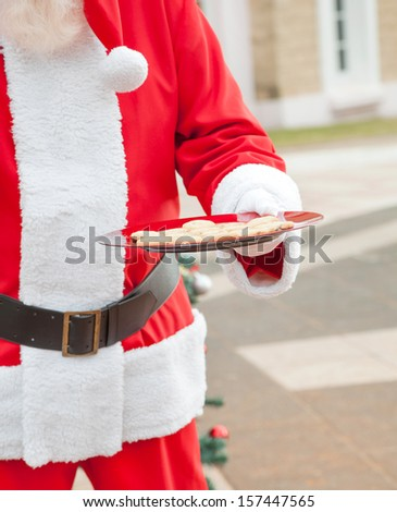 Midsection of Santa Claus holding plate with cookies in courtyard - stock photo