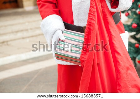 Midsection of senior man dressed as Santa Claus putting gift in bag outdoors - stock photo