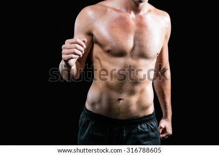Midsection of shirtless athlete running against black background