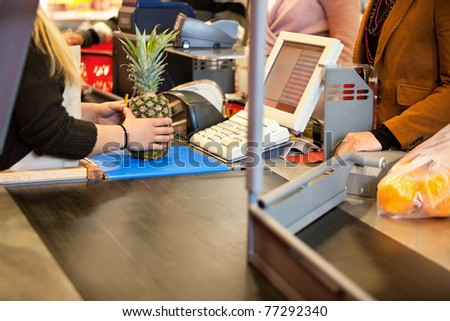 Midsection of shop assistant and customer in the supermarket - stock photo