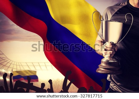 Midsection of successful rugby player holding trophy and ball against large football stadium under cloudy blue sky - stock photo