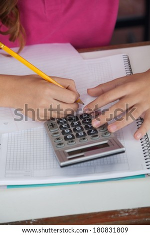 Midsection of teenage schoolgirl using calculator while writing at desk in classroom - stock photo