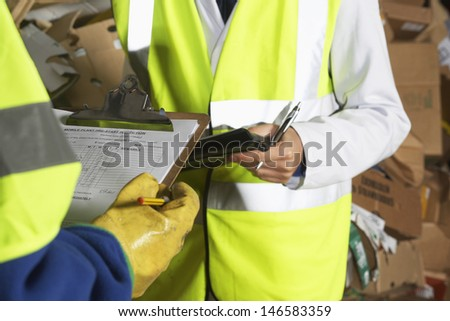 Midsection of two workers holding clipboards in industry - stock photo