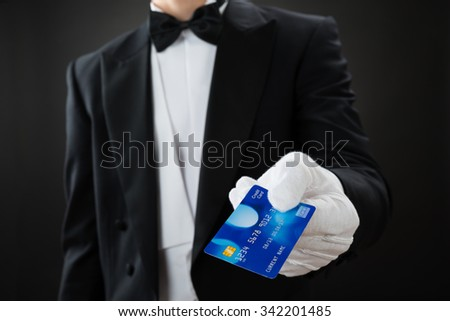 Midsection of waiter holding credit card against gray background - stock photo