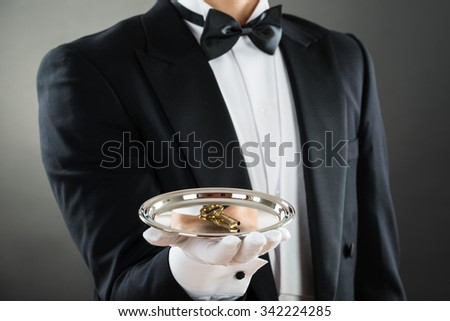 Midsection of waiter holding tray with keys while standing against gray background - stock photo