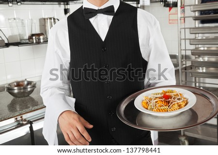 Midsection of waiter with pasta dish in commercial kitchen