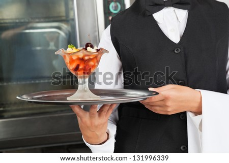 Midsection of waitress holding dessert tray at industrial kitchen - stock photo