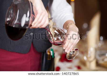 Midsection of waitress pouring red wine in wineglass from decanter - stock photo