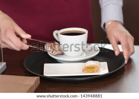 Midsection of waitress serving sweet food with coffee at table - stock photo