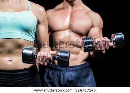 Midsection of woman and man exercising with dumbbells against black background - stock photo