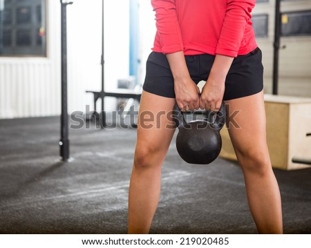 Midsection of woman exercising with kettlebell in cross training box - stock photo