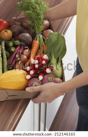 Midsection of woman holding container full of fresh vegetables at kitchen counter