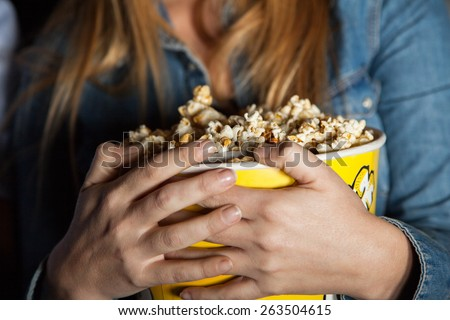 Midsection of woman holding popcorn bucket at cinema theater - stock photo