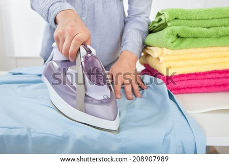 Midsection of woman ironing shirt at home - stock photo