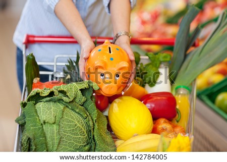 Midsection of woman keeping piggybank in shopping cart full of groceries at store - stock photo
