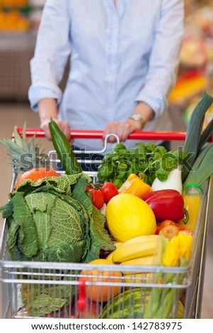 Midsection of woman pushing shopping cart in grocery store - stock photo