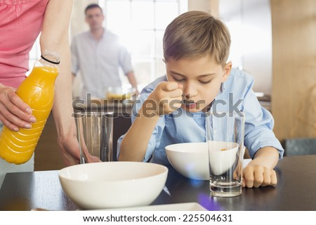 Midsection of woman with juice bottle standing by son having breakfast with man in background - stock photo