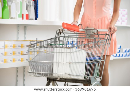 Midsection of woman with shopping cart buying beauty product in store