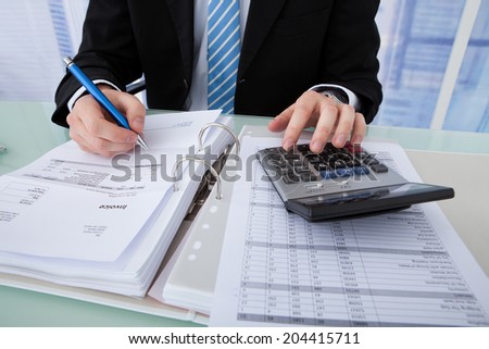 Midsection of young businessman calculating invoice at office desk - stock photo