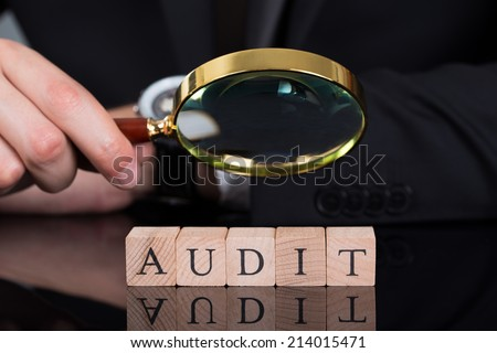 Midsection of young businessman examining Audit blocks through magnifying glass on desk - stock photo