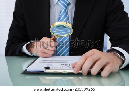 Midsection of young businessman examining invoice through magnifying glass at office desk - stock photo